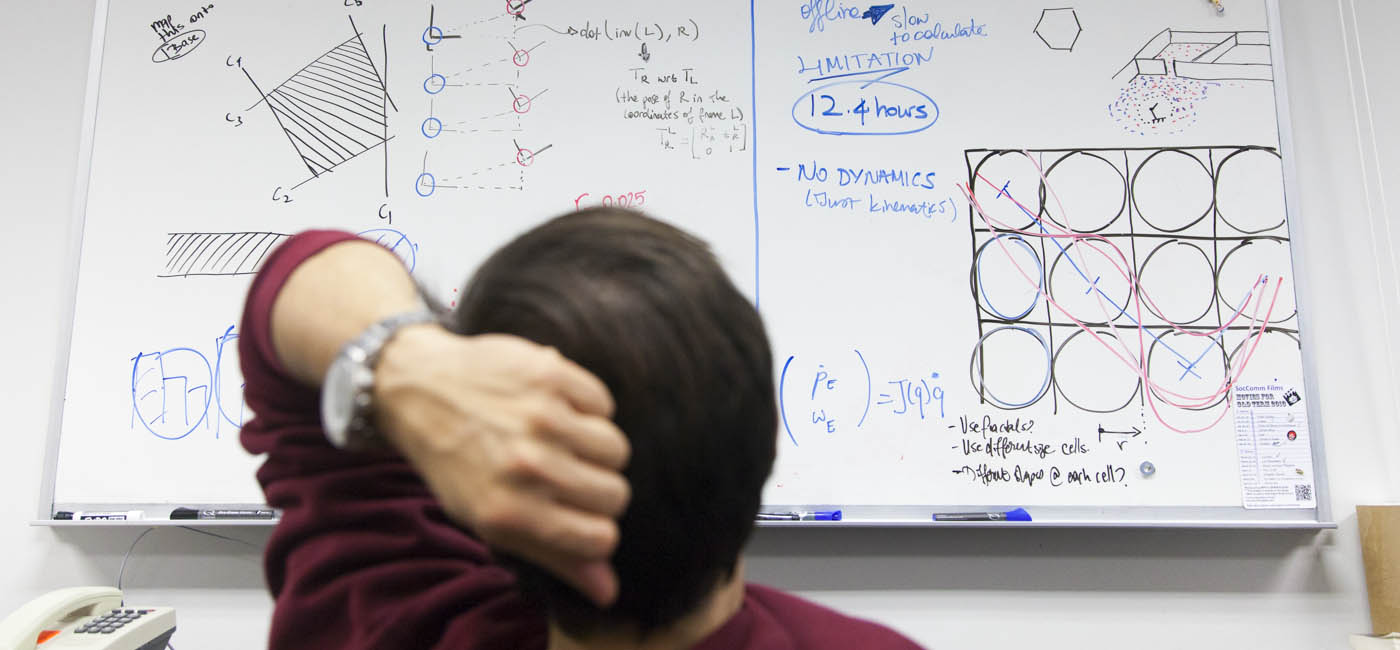 Person looking at drawings and calculations on whiteboard