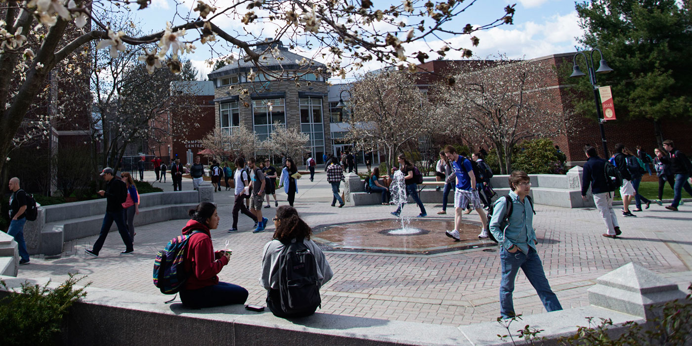 Students walking around the fountain in the springtime
