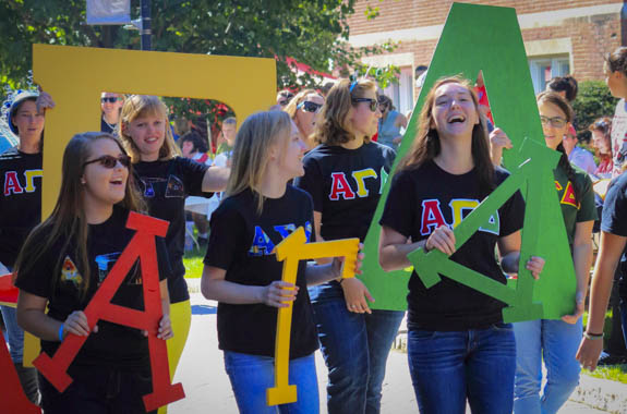 Students holding Greek letters at parade