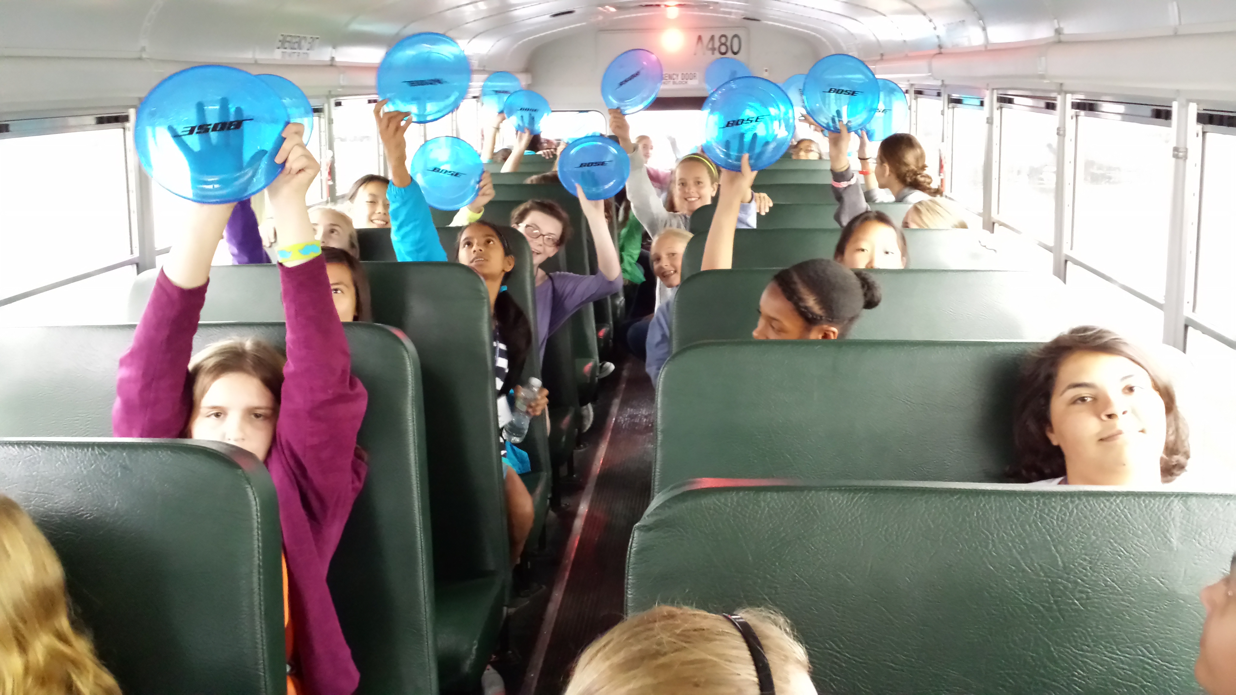 "Camp Reach, girls on a bus holding up ""Bose"" frisbees."
