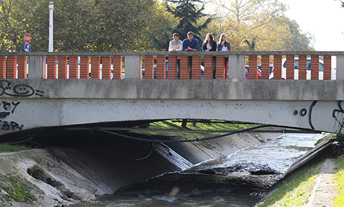 Students on a bridge in Tirana inspecting the quality of the water