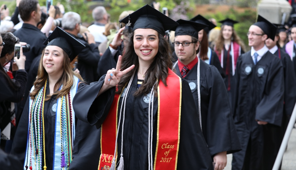 A female member of WPI's undergraduate Class of 2017 crosses the Earle Bridge and gives the victory sign