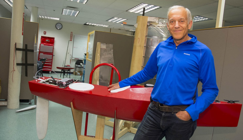 Ken Stafford stands next to his red Sailbot.