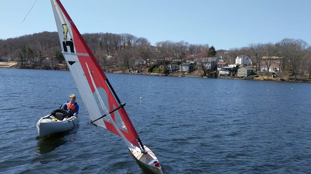 WPI senior Tucker Martin tests the robotic sailboat on Lake Quinsigamond.
