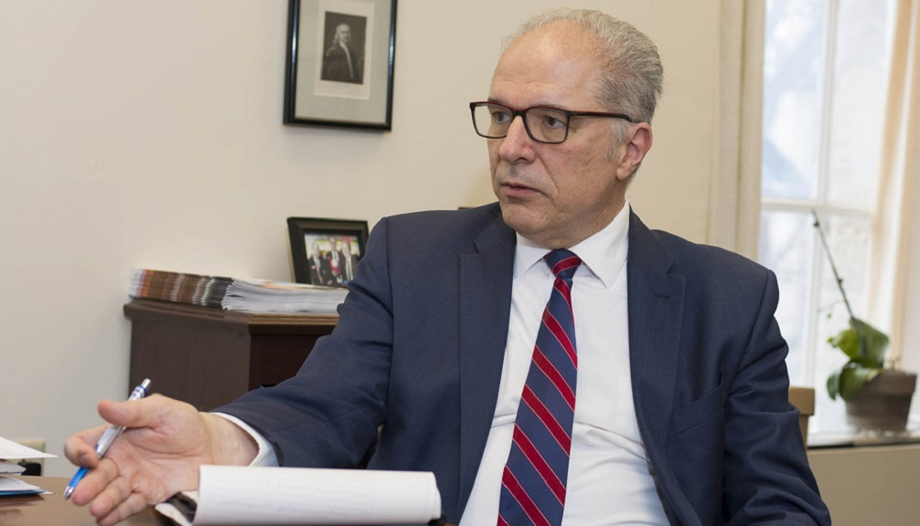 Bogdan Vernescu, wearing brown glasses, a dark blue suit jacket, white button-down shirt, and red and white striped tie, sits at a desk and is in mid-discussion.