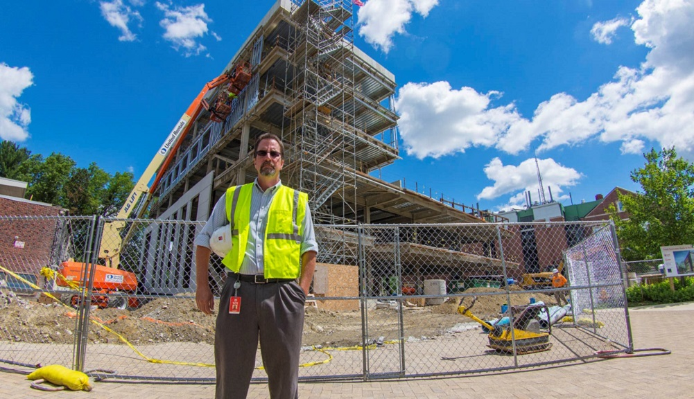 Jim Bedard wears a fluorescent yellow safety vest over a light blue button-up shirt and gray slacks. He is holding a white hard hat under one arm, and is standing in front of the Foisie Innovation Studio construction site.