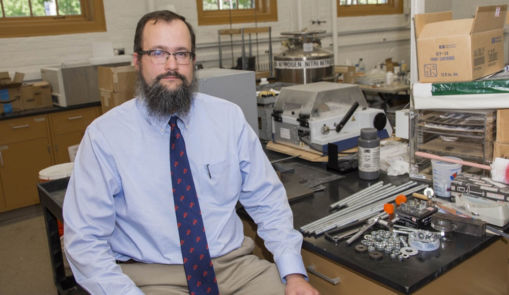 Aaron Sakulich is sitting at a lab table with a pile of small metal pieces and rods next to him. He's got dark hair, a beard, and glasses, and is wearing khaki pants, a light blue button down shirt, and a dark blue tie with red lobsters.