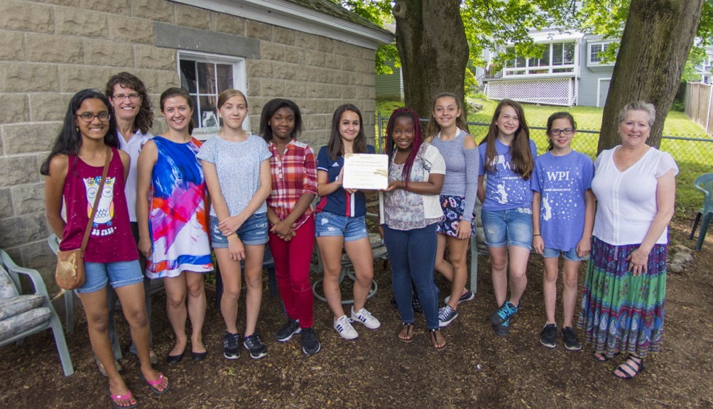 Nine young girls from Camp Reach, Joanne Alley, and Chrysanthe Demetry pose with a certificate.