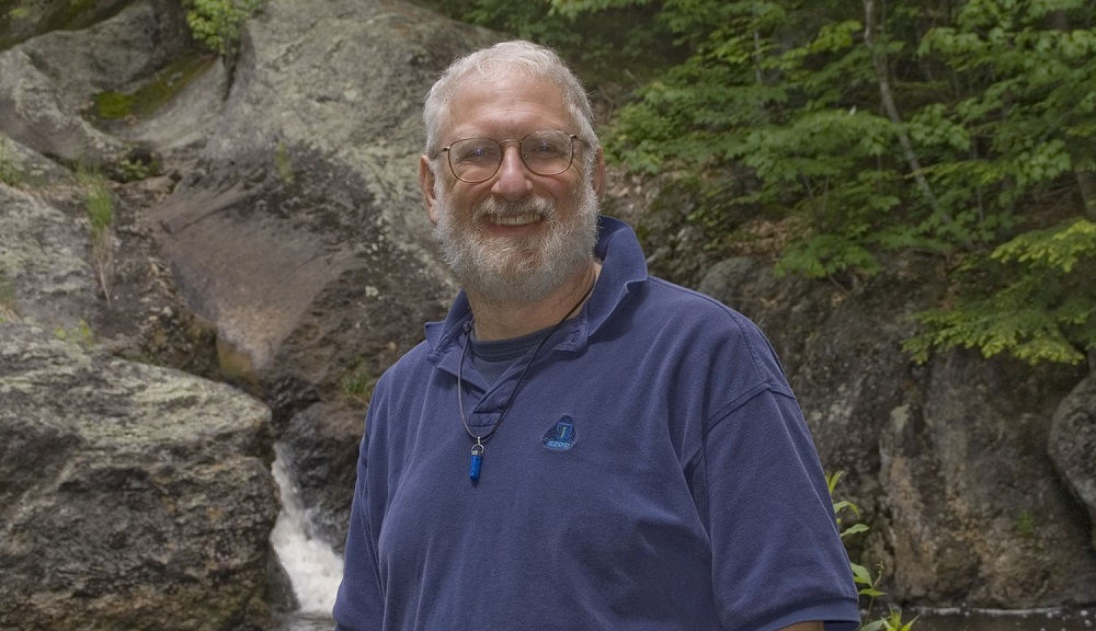 Roger Gottlieb stands in front a rock formation with running water and green foliage in the background. He's smiling, has white hair and beard, and is wearing glasses and a dark blue polo shirt.