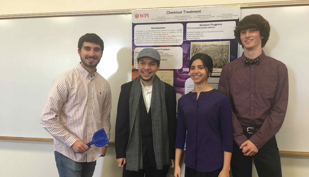 Four students (two young men, a young woman, and another young man) pose, smiling, in front of their poster on chemical treatment. The young man on the left is holding a blue shovel.