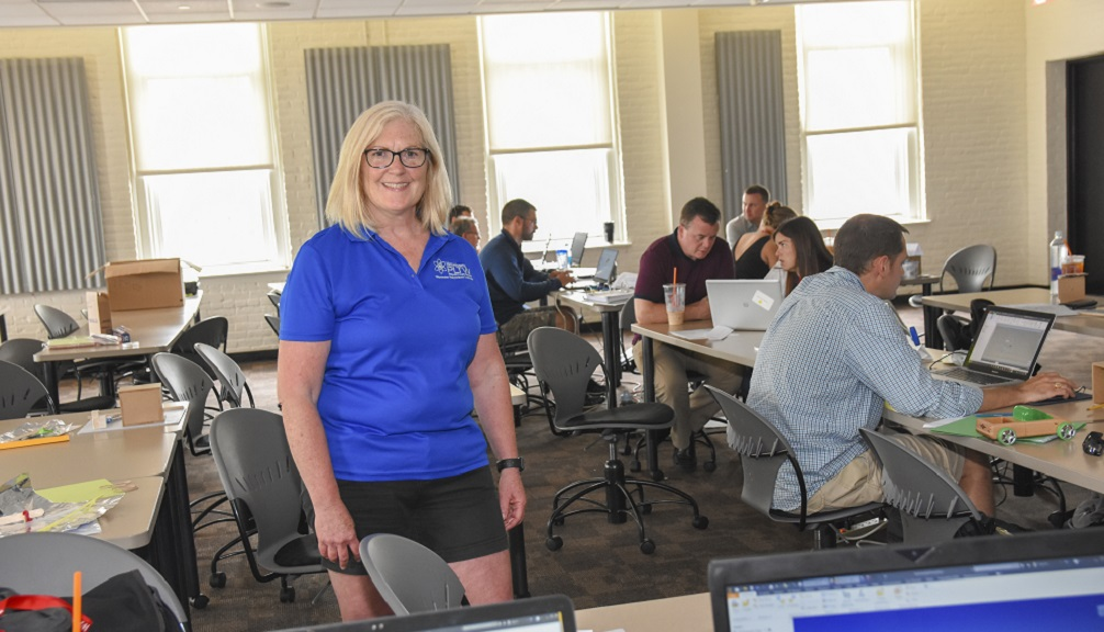 Martha Cyr stands in the middle of a classroom with students and faculty members working on laptops in the background. She is smiling and has blonde hair, and is wearing glasses, a short-sleeved dark blue shirt, and black shorts.