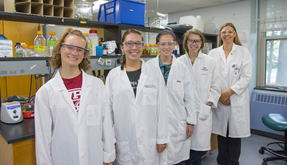 Four young women (part of the iGEM team) in front of a lab station, with Natalie Farny standing behind them. They're all smiling and wearing white lab coats and safety glasses.