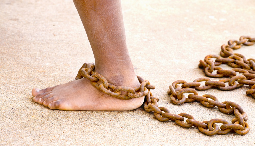 A human foot and calf are shown, with rusted chains wrapped around the ankle.