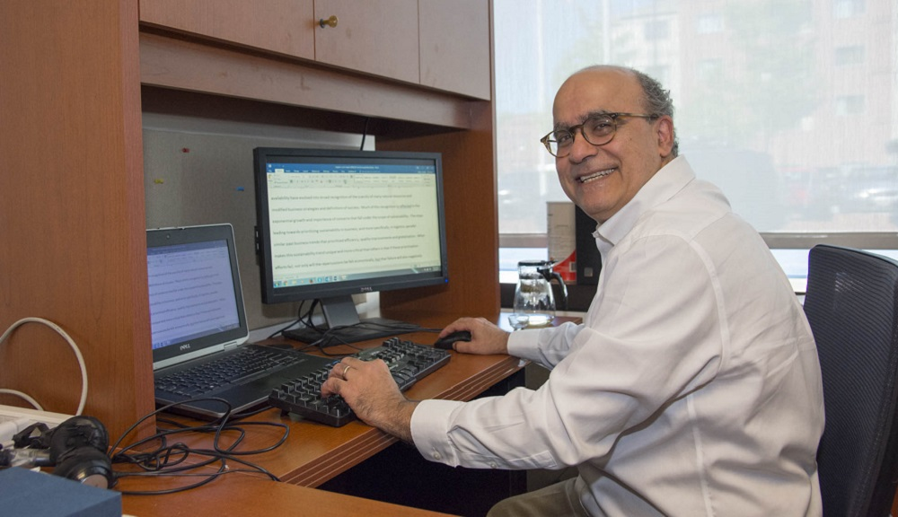 Joe Sarkis sits at his desk with two computer monitors in front of him. He's got one hand on the keyboard and one on the computer mouse, and is looking over his shoulder and smiling. He has gray hair and is wearing glasses.