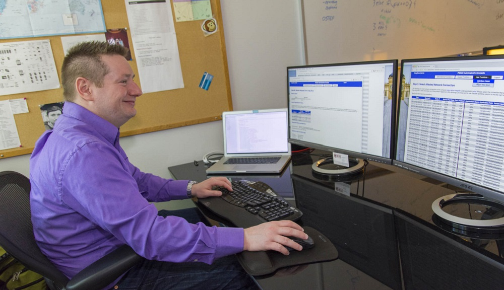 Craig Shue sits in front of two computer monitors and a laptop. He's smiling, and is wearing a purple shirt and dark blue jeans.