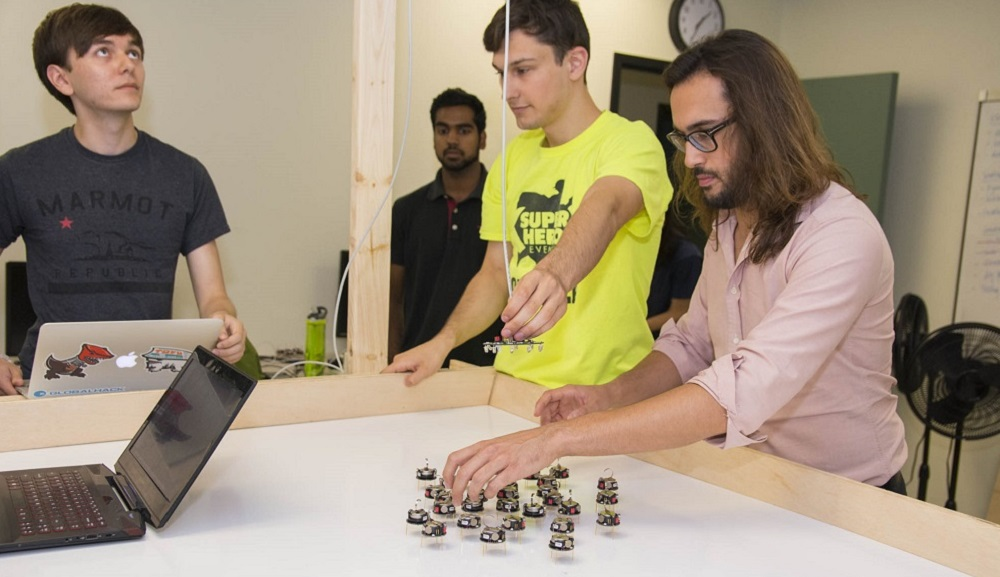 Carlo Pinciroli (right) adjusts the swarm robots while three of his students look on. He's wearing a light pink shirt, and the students are wearing blue, black, and yellow T-shirts.