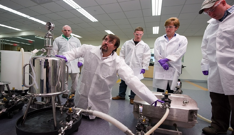 An instructor in white lab coat empties a bioreactor while students in white lab coats in the background observe