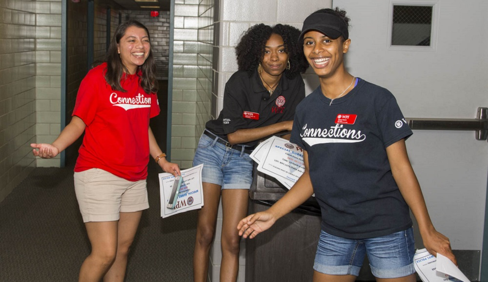 Three female students prepare for move-in day. They're all smiling, and are wearing red and blue T-shirts.