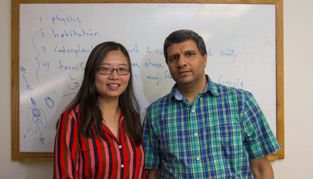 Shanshan Rodriguez and Rudra Kafle stand in front of a white board. Shanshan is wearing a pink, red, black, and brown striped blouse; Rudra is wearing a blue, green, and pale yellow checkered shirt.