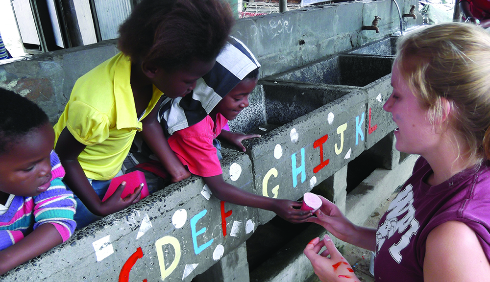 A student hands children a sponge with paint on it. A wall with the ABCs written in paint is in the middle of the photo.