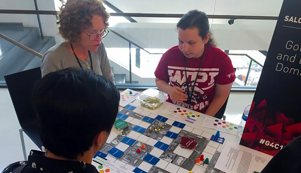 Two attendees of the Games for Change Festival gather around a table to play a board game developed by a WPI student, who looks on to provide instructions and tips.