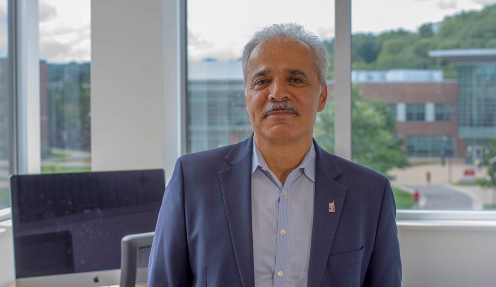 Siamak Najafi stands in front of windows that overlook the Quad. There is a Mac computer in the left corner. Najafi has gray hair and mustache, and is wearing a dark blue blazer and light blue button-up shirt.