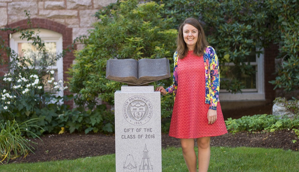 Tracy Baldelli stands next to the Bill Grogan Memorial. She is smiling and wearing a coral dress and bright, multicolored blazer.