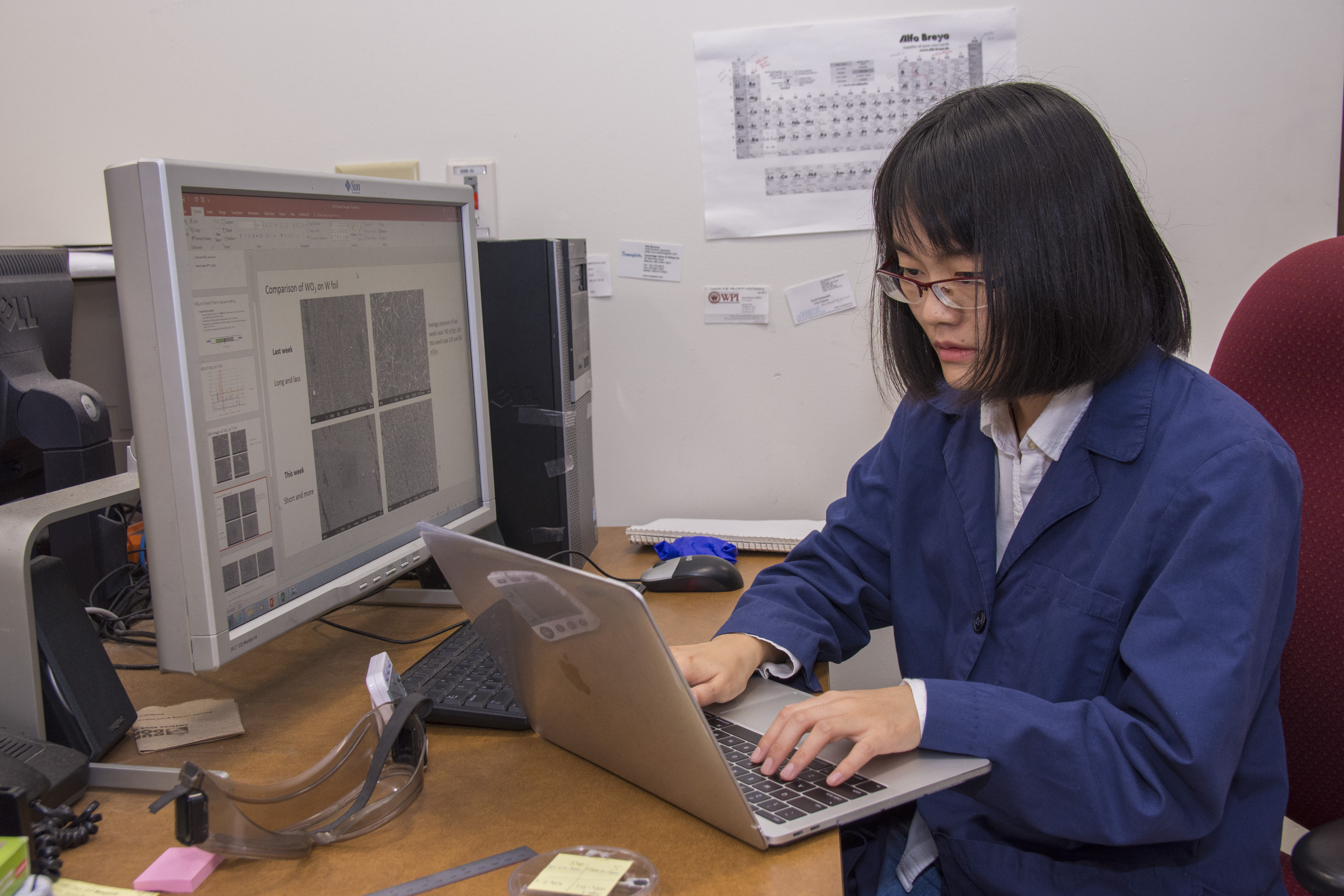 PhD student Tao Yan works at a labtop while a computer monitor next to her displays images of the nanostructure of materials.
