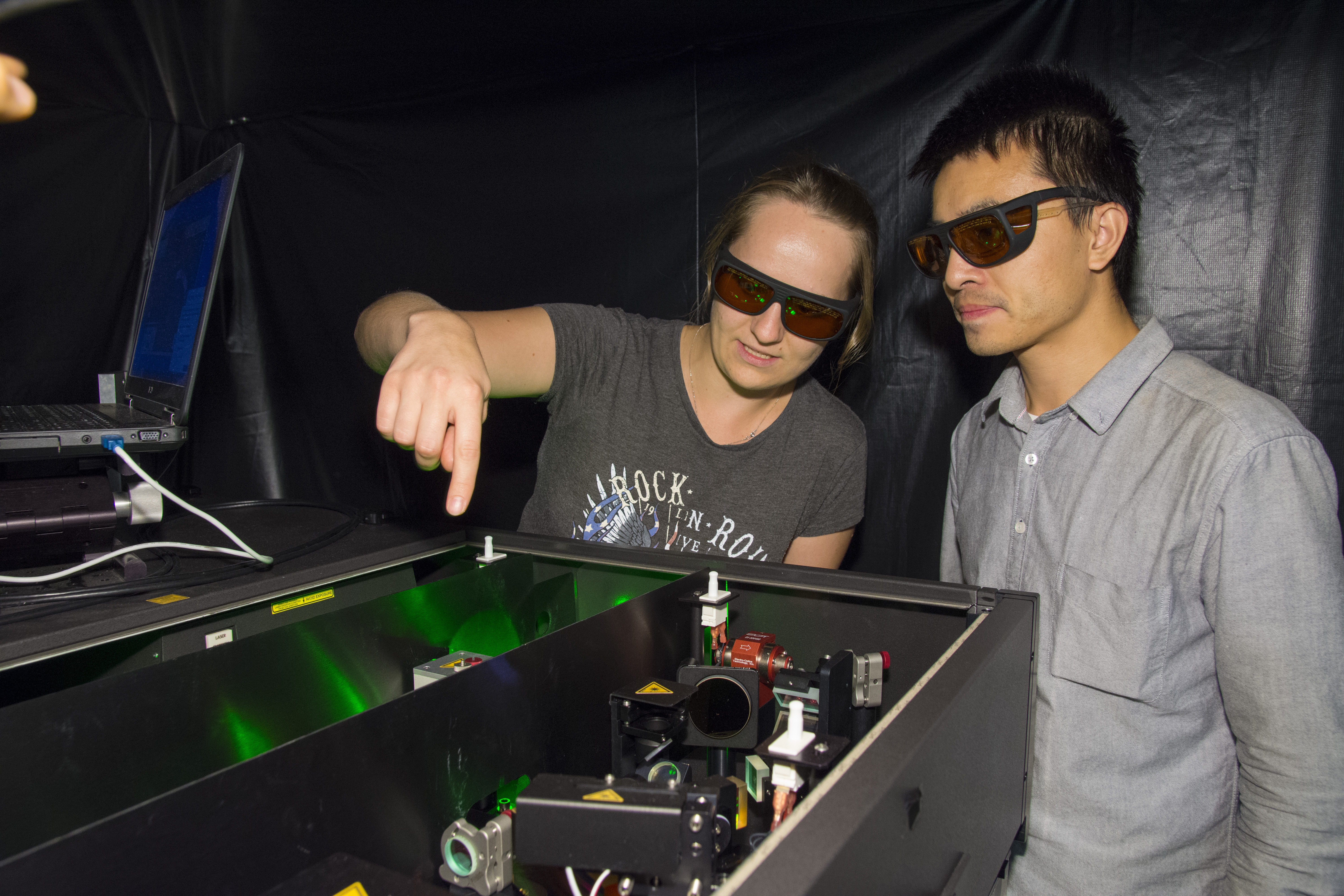 Physics PhD students Kateryna Kushnir, left, and Guangjiang Li, both wearing red-tinger safety glasses, examine the lasers inside an apparatus in the Terahertz Physics Lab.