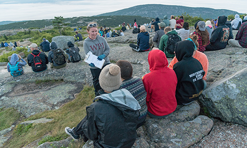 Students sit on rocks, facing the mountain views of Acadia National Park. One student stands in front of the rest, holding a clipboard.