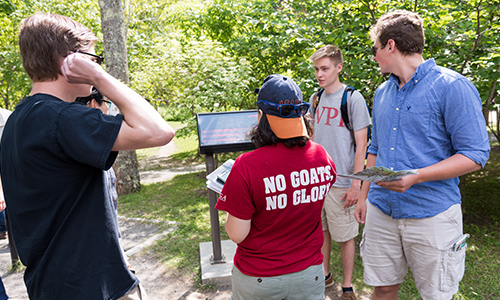 WPI students are gathered around an entrance to Acadia National Park, surrounded by trees and other foliage.