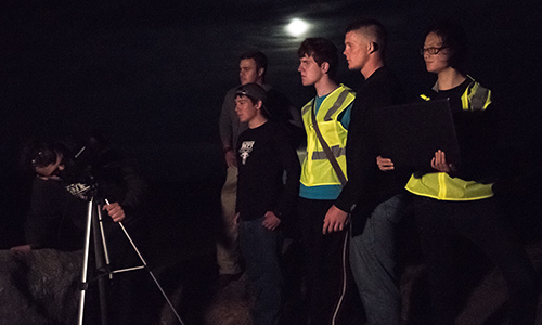 Students wear neon yellow vests and observe the night sky from the top of one of the mountains in Acadia National Park.