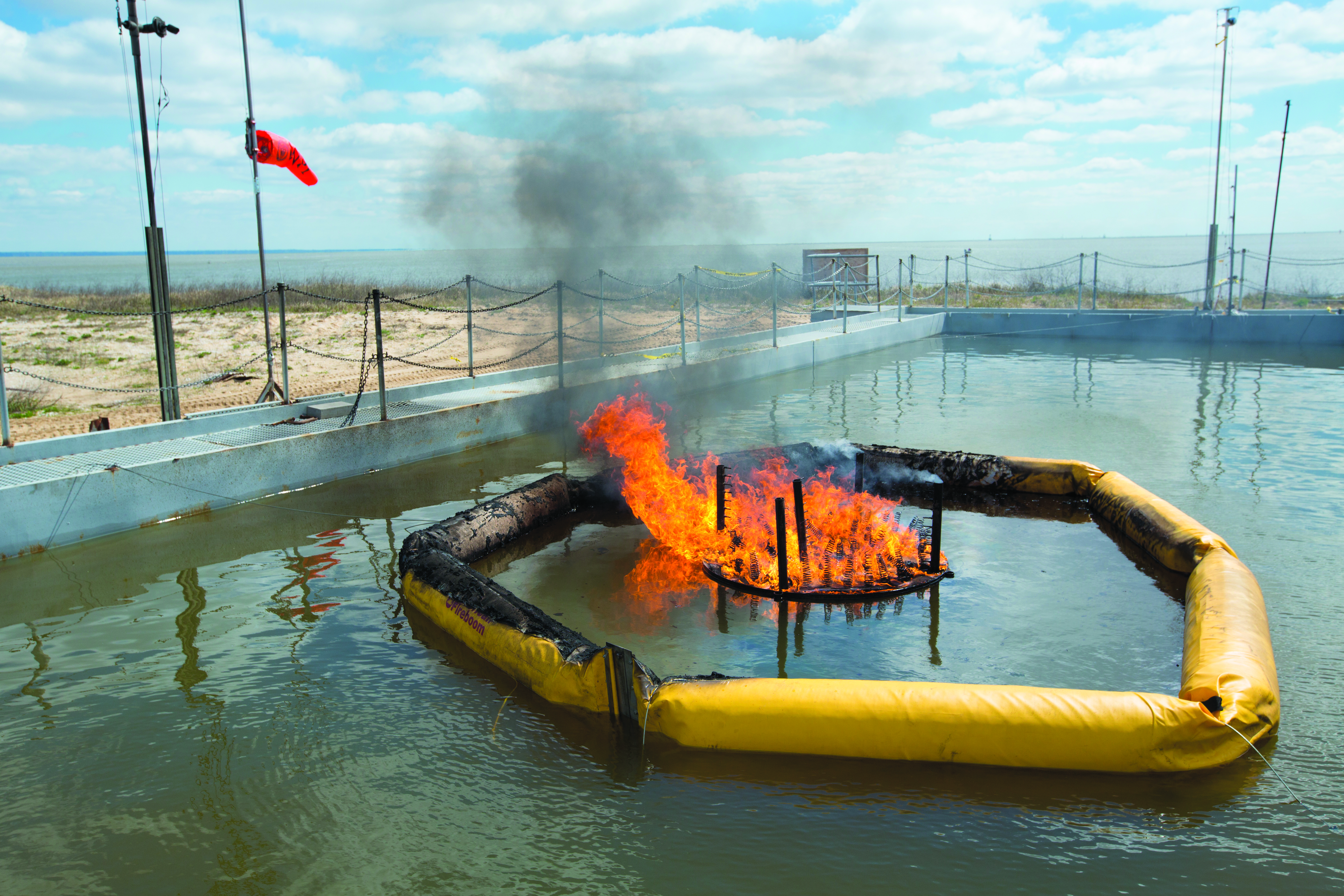 The Flame Refluxer surrounded by a yellow oil boom burns inside the burn pan on Little Sand Island
