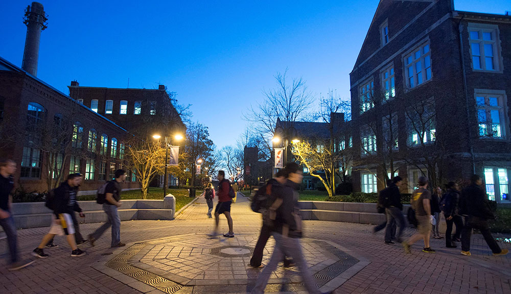 Students walking past fountain in the evening.