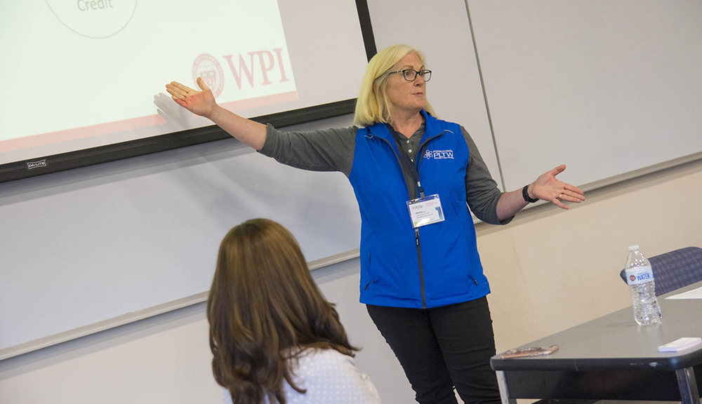 Martha Cyr stands in front of a projection and addresses a class. She's gesturing toward the projection, has blonde hair, and is wearing glasses, a blue vest, gray shirt, and black pants.