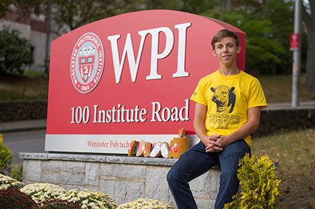 Ari Trey-Masters sits next to the sign at WPI's main entrance. He's wearing a yellow Cheese Club shirt with a cow on it and jeans, and has several blocks of cheese next to him.