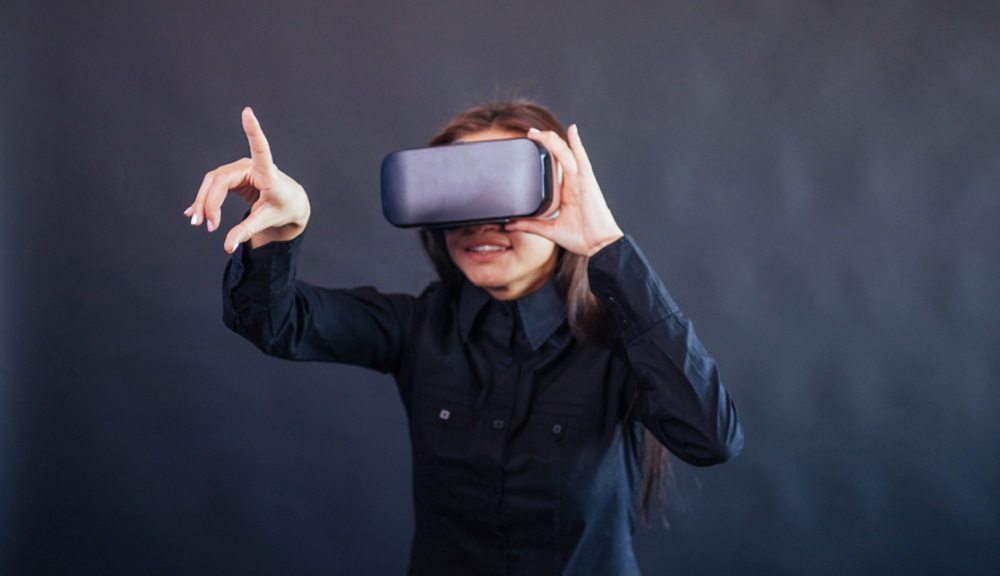 A woman uses a virtual reality headset against a dark background.