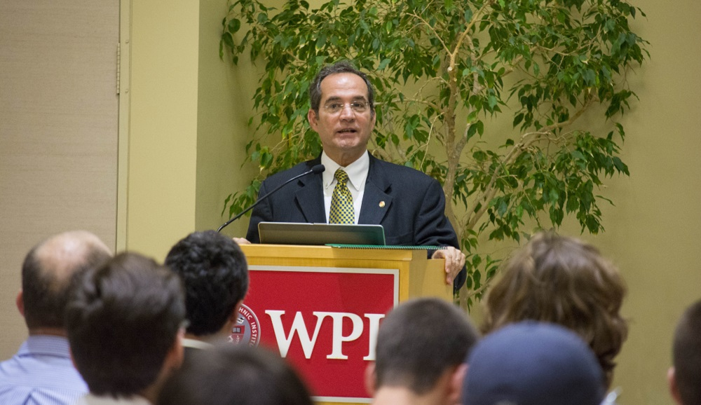 Martin Burt addresses a crowd standing at a podium emblazoned with WPI's logo. He is wearing a dark suit, white shirt, and green and gold tie.