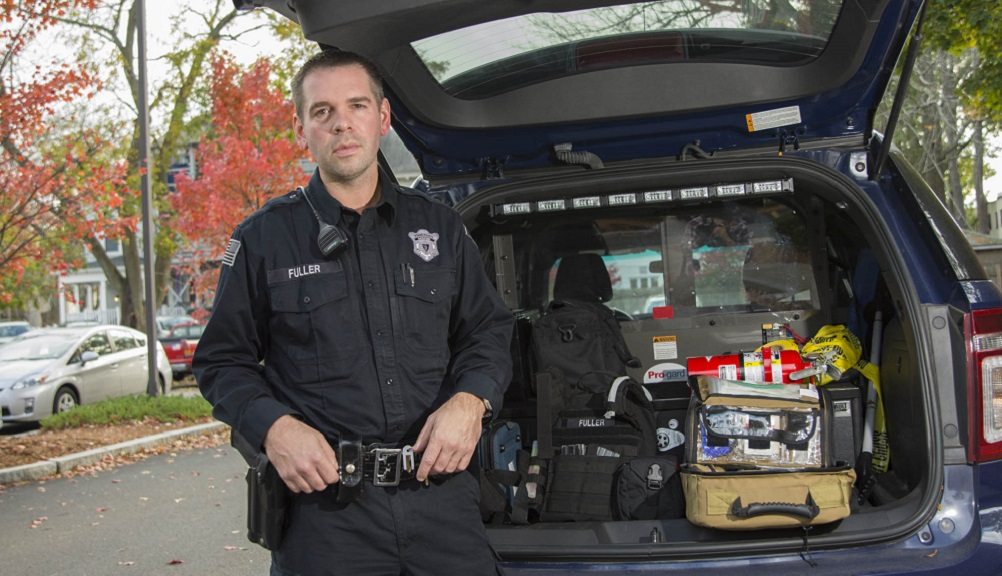 Officer Fuller in front of a WPI Police cruiser. He's wearing a dark navy police uniform, and crisis management equipment is loaded into the back of the vehicle.