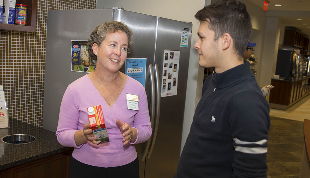 Shavaun Cloran reviews nutrition facts with a student. She is wearing a pink sweater, and he is wearing a dark shirt. She's holding a carton of almond milk, and they're in the Morgan Dining Hall.