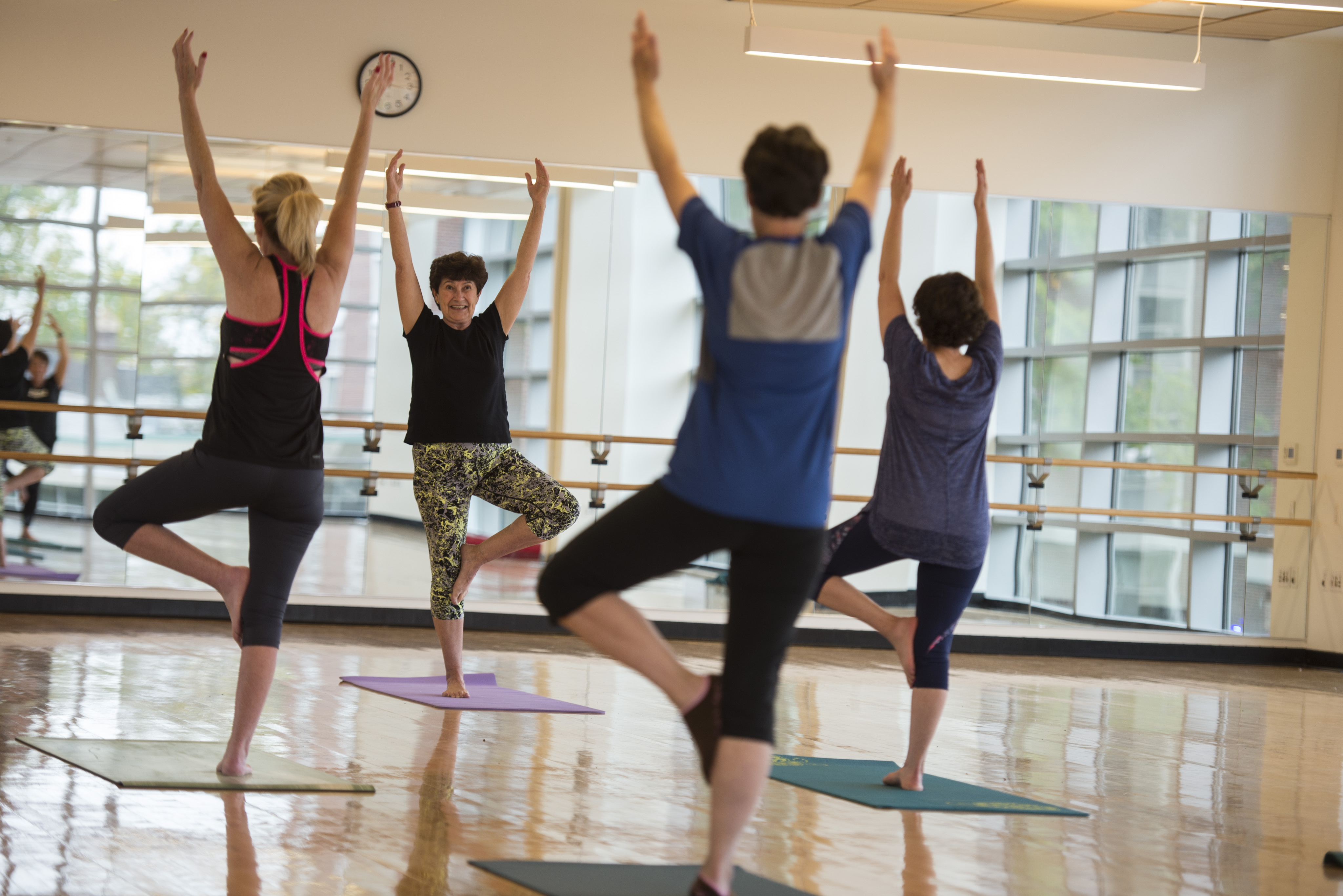 women in a yoga class facing the teacher wearing workout clothes with their arms raised over their heads and balancing on one foot
