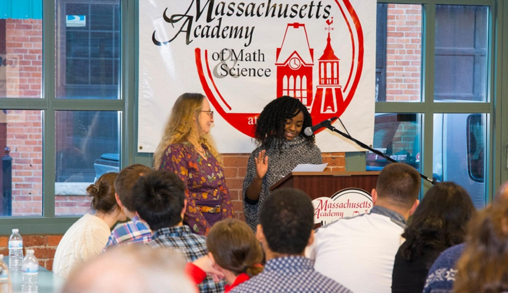 A student stands at the podium addressing a former teacher. They're in front of a brick wall and a banner with the Mass Academy logo, and two large windows.