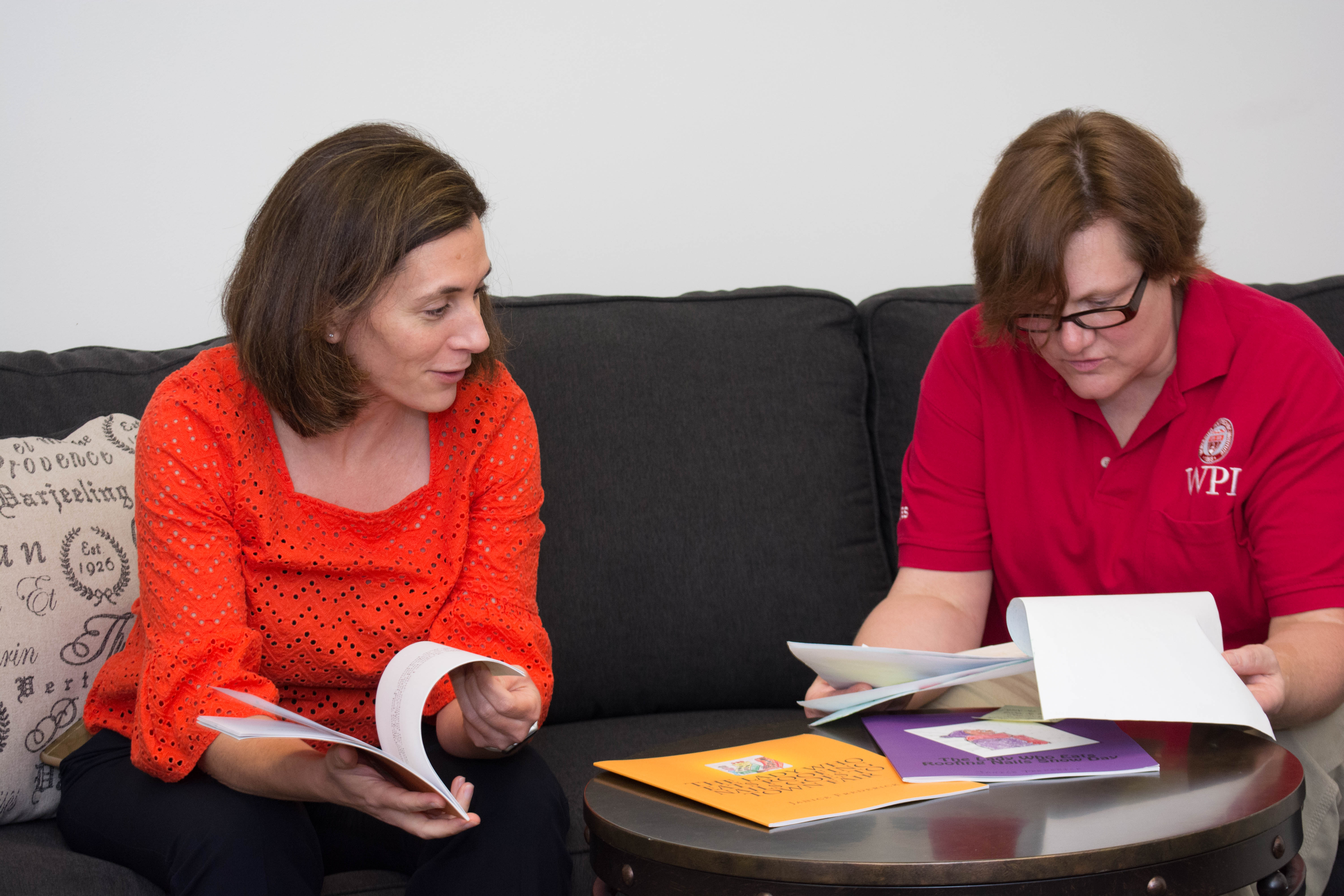 Two women, one in an orange shirt on the left and one in a red shirt on the right, sitting on a couch, smiling, and looking through books.