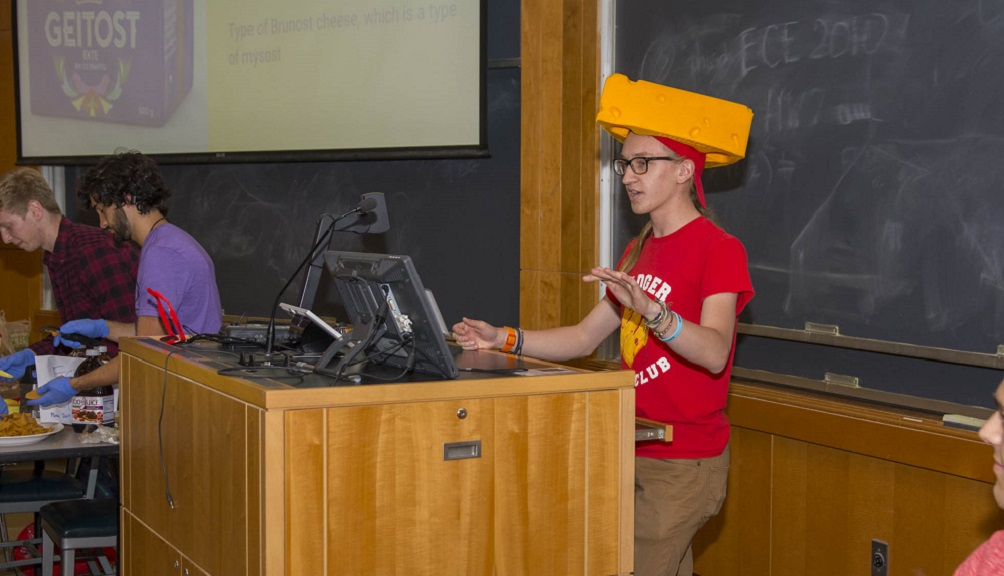 A student wearing a red shirt and yellow cheese head stands at a wooden podium, while two other students prepare cheese in the background.