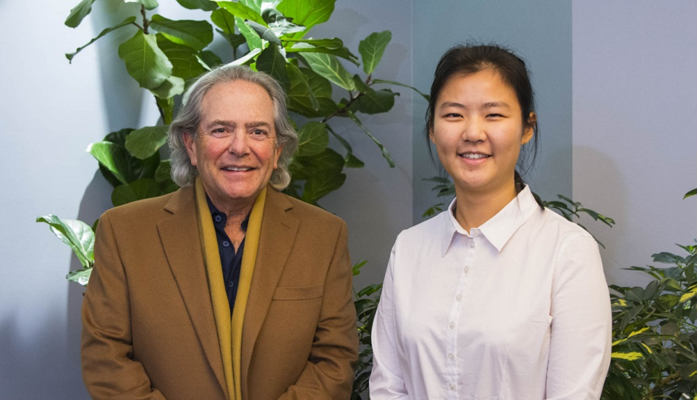 Weijia Tao following the Kalenian Awards Ceremony. She is wearing a white blouse and smiling, and is standing next to a man with gray hair and a brown coat.