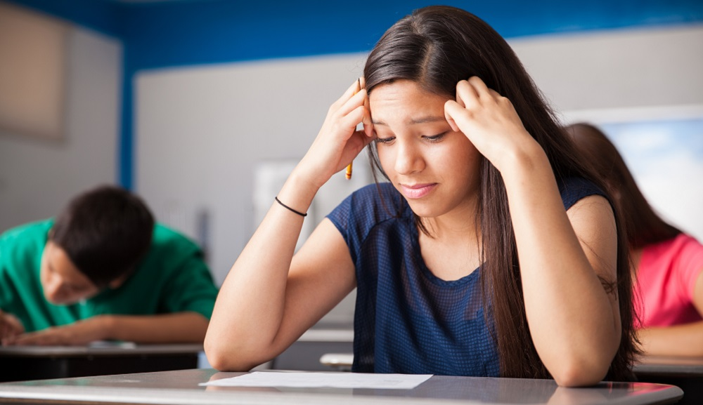 A female student studies a test on her desk. She looks concerned, and is pressing her forehead against her fists.