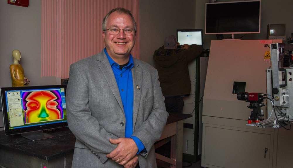 Doug Petkie stands in a lab, with a computer screen (showing a heat map) and other equipment behind him, as well as a man working on a computer. He's smiling and is wearing glasses, a gray suit jacket, and blue button-up shirt.