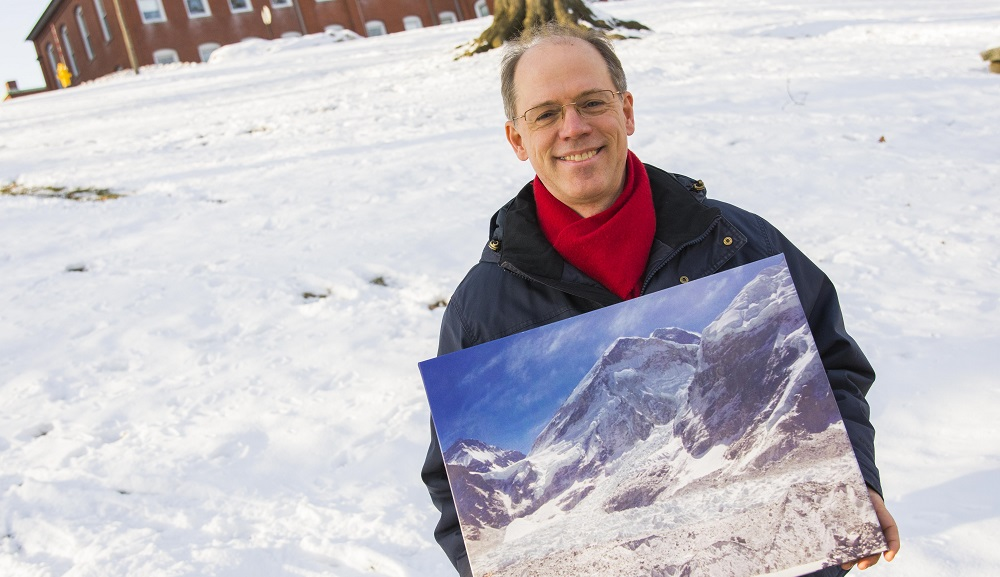 Peter Hansen stands in front of a snow-covered Boynton Hill, holding a painting of Mt. Everest. He's smiling, and is wearing glasses, a dark blue jacket, and red scarf.
