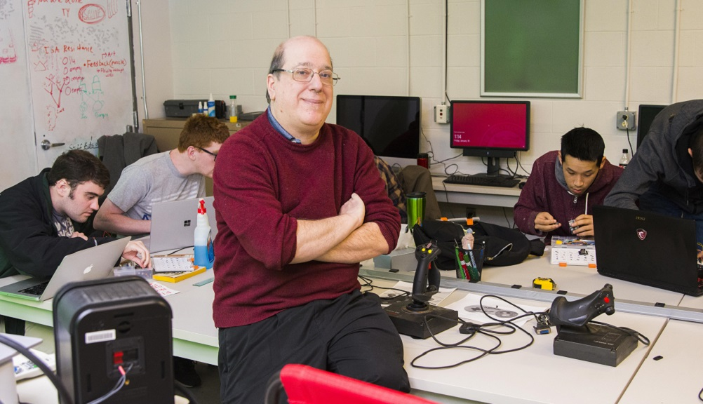 Jeff Kesselman sits on the edge of a table with gaming equipment on it while students work in the background. He's smiling and is wearing dark pants, glasses, and a red sweater.