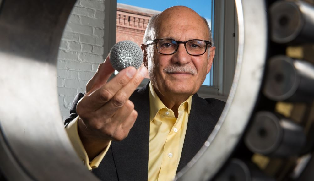 Diran Apelian looks through a large bearing while holding a small globe made with additive manufacturing